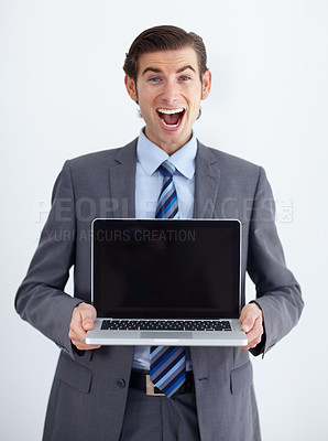 Buy stock photo A young businessman presenting a laptop to you excitedly