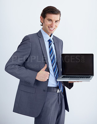 Buy stock photo A young businessman endorsing a laptop with a thumbs up