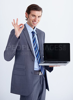 Buy stock photo A young businessman endorsing a laptop with an 'a okay' hand sign