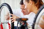 Man fixing a bicycle tyre with wife