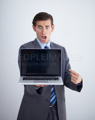 Buy stock photo Shocked young man holding a laptop and looking shocked against a white background