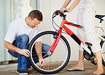 Man checking the tyre pressure of wife's new bicycle