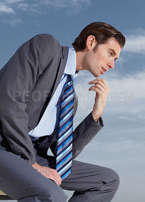 Buy stock photo A young businessman thinking deeply against a blue sky