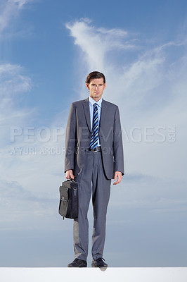 Buy stock photo Full body of a serious businessman standing against a blue sky
