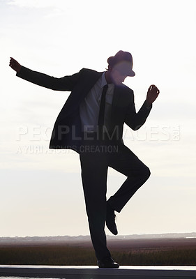 Buy stock photo Silhouette image of a young man in a suit dancing against the morning sky