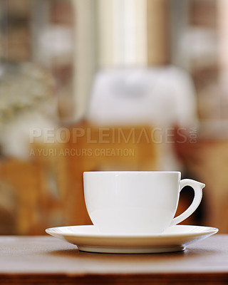 Buy stock photo Shot of a lone coffee cup sitting on a table in a cafe