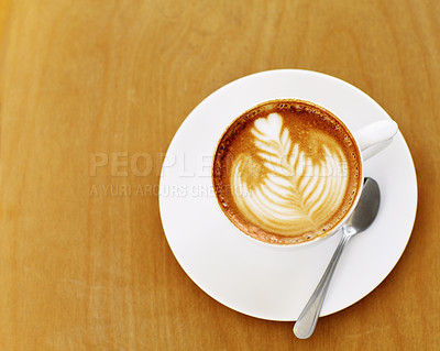 Buy stock photo High angle shot of an artistically prepared cup of cappuccino sitting on a cafe table
