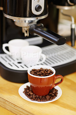 Buy stock photo Shot of a mug full of coffee beans sitting in front of an expresso making machine