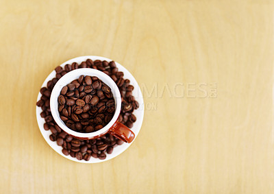 Buy stock photo High angle shot of a mug and saucer filled with coffee beans