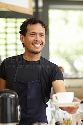 Buy stock photo Shot of a handsome barista serving up a fresh cup of coffee