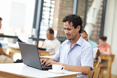 Buy stock photo Shot of a young man working on a laptop while sitting in a cafe