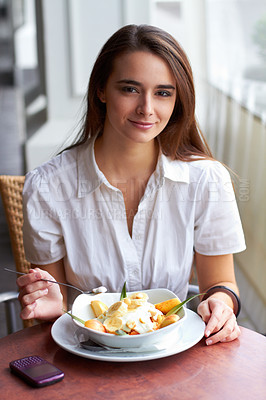 Buy stock photo Portrait of a happy young female eating fruit salad in a bowl