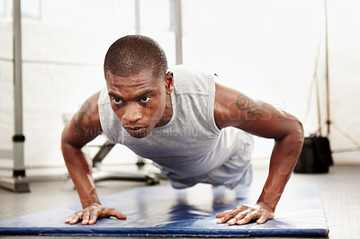 Buy stock photo Seriously focused man doing push ups in a gym