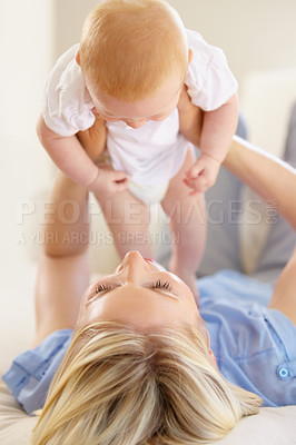 Buy stock photo An adorable baby girl being lifted into the air by her mother