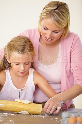 Buy stock photo A mother helping her daughter to rollout the cookie dough