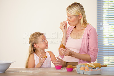 Buy stock photo A mother and daughter tasting the muffins they've baked