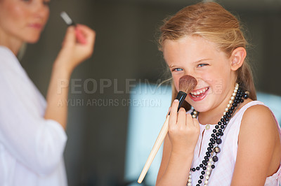Buy stock photo Little girl trying on her mother's makeup while her mother is in the background