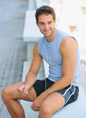 Buy stock photo Happy young jogger sitting outside and listening to music