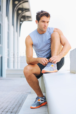 Buy stock photo Handsome young jogger tying his shoelaces