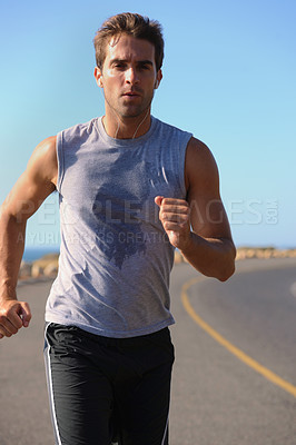 Buy stock photo Handsome young man jogging down the road