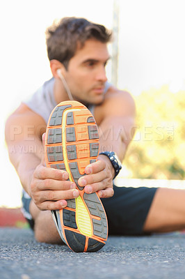 Buy stock photo Young jogger sitting and stretching while looking sideways