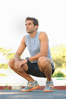 Buy stock photo Handsome young runner squatting down while listening to music