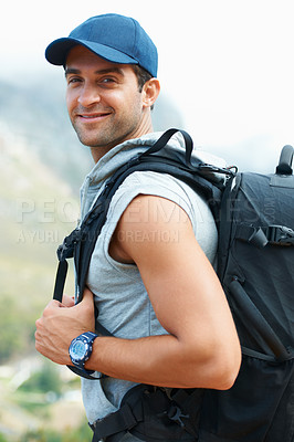Buy stock photo Happy young hiker looking over his shoulder at the camera