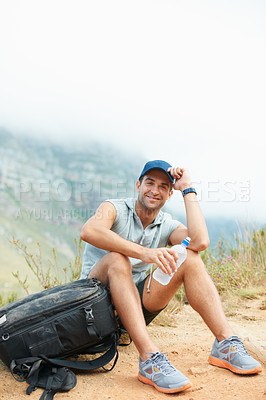Buy stock photo Young hiker sitting and smiling at the camera while taking a break