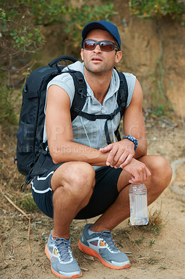 Buy stock photo Young hiker taking a break and holding a water bottle