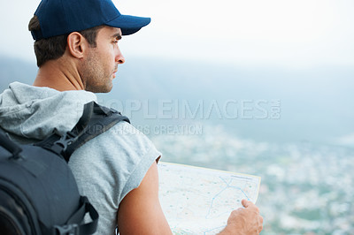 Buy stock photo Young hiker holding a map and looking at the scenic view