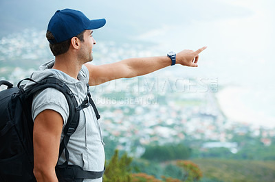 Buy stock photo Young male hiker pointing towards the ocean view - copyspace