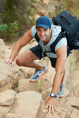 Buy stock photo Young hiker climbing up a cliff - portrait