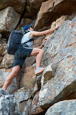 Buy stock photo Young mountain climber scaling a rock face