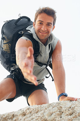 Buy stock photo Handsome young mountain climber extending his hand towards the camera