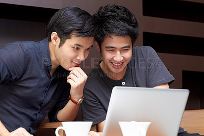 Buy stock photo Two young Asian guys surfing the web together on a laptop