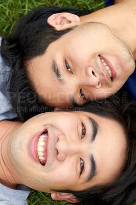 Buy stock photo Cute young gay Asian couple smiling together and looking up at the camera