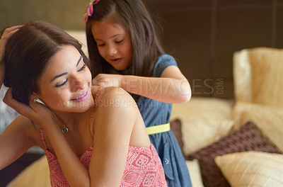 Buy stock photo Little sister helping her big sister get dressed