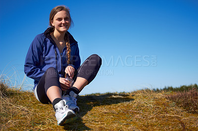 Buy stock photo Shot of a young woman resting after her outdoors workout