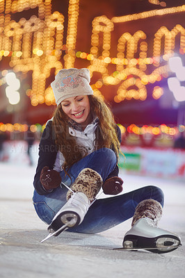 Buy stock photo Shot of a young woman sitting on the ice of a skating rink tying the laces of her ice skates