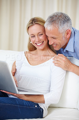 Buy stock photo An attractive young woman using her laptop with her husband standing behind her