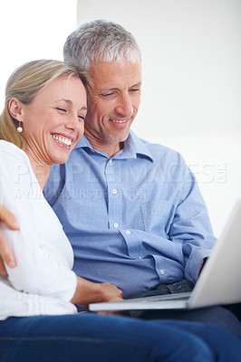 Buy stock photo A young couple looking content as they share a laptop
