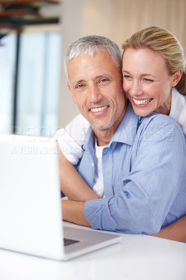 Buy stock photo A woman hugging her husband as he works on the laptop at home