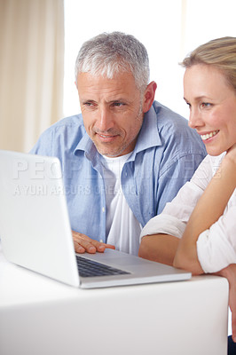 Buy stock photo A mature couple looking relaxed as they work on the laptop at home