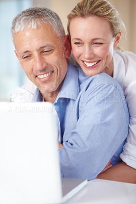 Buy stock photo A happy woman embracing her husband as he works on his laptop