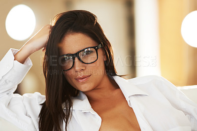 Buy stock photo Beautiful young brunette wearing glasses and an unbuttoned white shirt while sitting on the couch