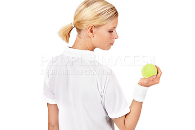 Buy stock photo An attractive young woman holding and looking at a tennis ball