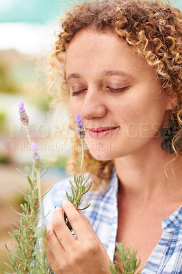 Buy stock photo A cute young woman smelling a sprig of lavender
