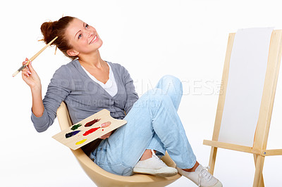 Buy stock photo Studio shot of a young woman holding a palette and brush looking for inspiration