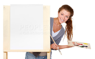 Buy stock photo Studio shot of a young woman holding a palette and brush and standing with an easel