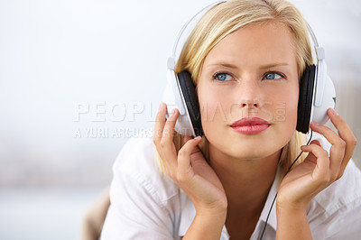 Buy stock photo Shot of an attractive young woman lying down and listening to music